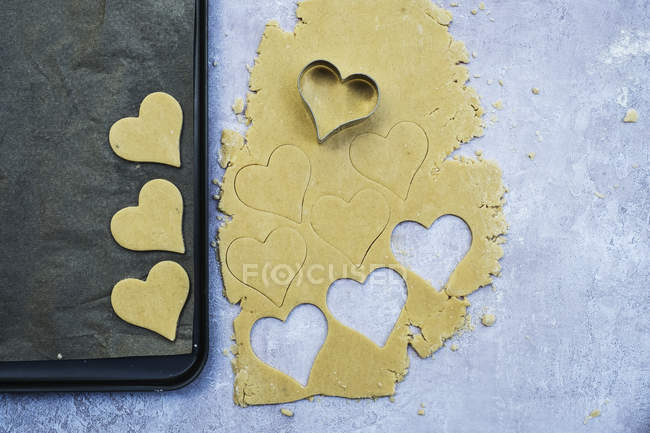 High angle close-up of heart-shaped cookies cut out of cookie dough. — Stock Photo
