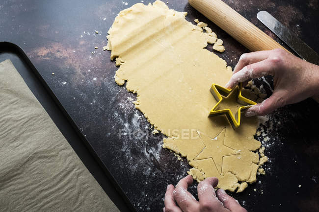 High angle close-up of cook cutting out star-shaped cookies from cookie dough. — Stock Photo