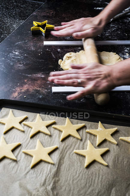 High angle close-up of male cook rolling dough for star-shaped cookies using guide rods to maintain even thickness of dough. — Stock Photo