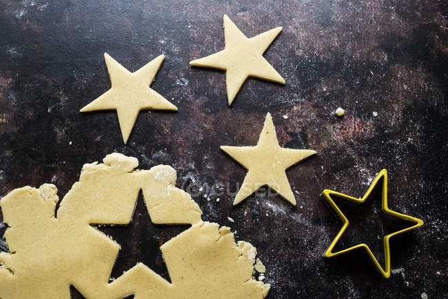 High angle close-up of star-shaped cookies cut out of cookie dough. — Stock Photo