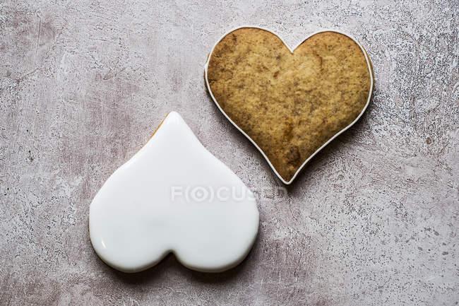 Plan rapproché d'angle élevé de deux biscuits fraîchement cuits en forme de coeur décorés avec le glaçage blanc. — Photo de stock