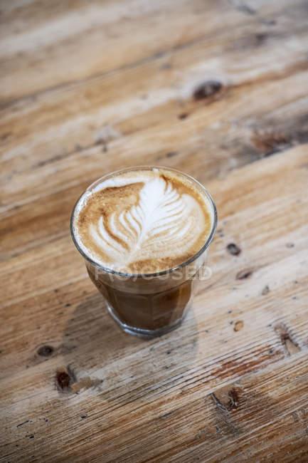 Високий кут крупним планом склянки кавового латте на дерев'яному столі. — стокове фото