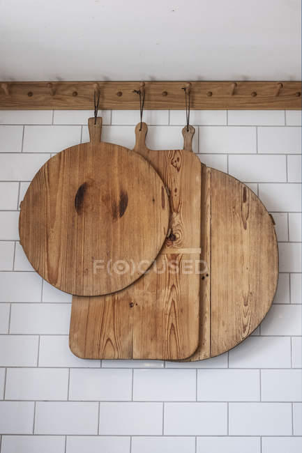 Piccola selezione di taglieri in legno appesi alla parete bianca piastrellata . — Foto stock