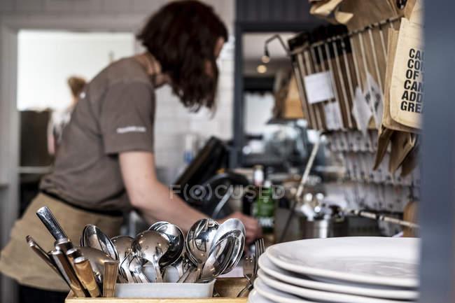 Primer plano de pila de platos y contenedor con cubiertos en restaurante, mujer trabajando en segundo plano . - foto de stock