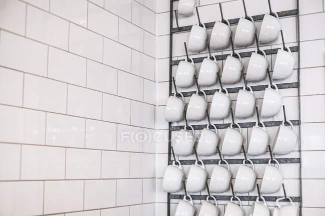 Крупний план білих капучіно гуртки, що висять на металевій стійці на білій черепичної стіні. — стокове фото