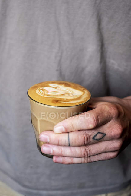 Close-up of person with tattooed fingers holding glass of coffee latte. — Stock Photo