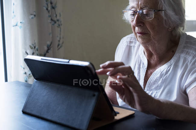Senior woman sitting at table and using digital tablet with touch screen. — Stock Photo
