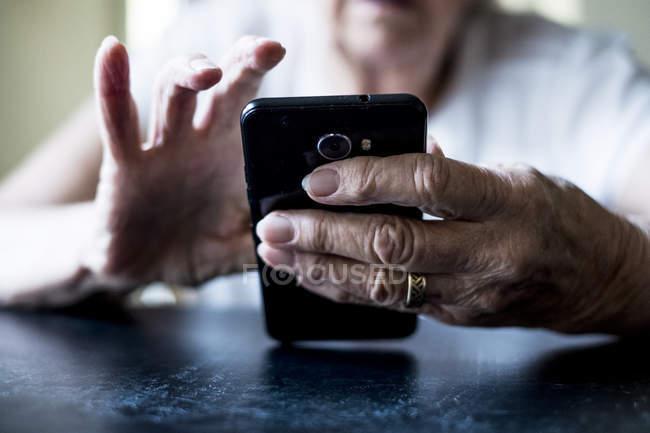 Plan rapproché des mains de femme aînée s'asseyant à la table et utilisant le téléphone portable. — Photo de stock