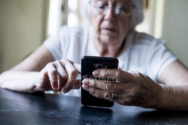 Primer plano de las manos de la mujer mayor sentada en la mesa y usando el teléfono móvil . - foto de stock