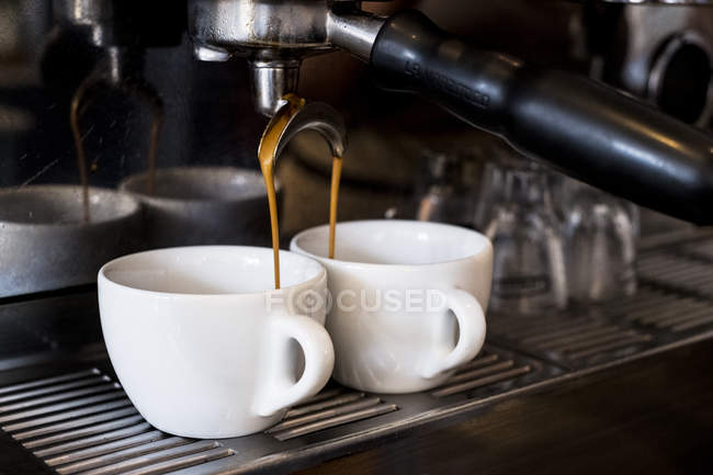 Close-up of commercial espresso machine in coffee shop pouring coffee in cups. — Stock Photo