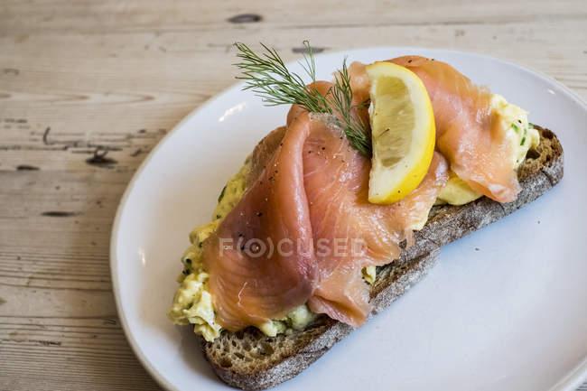 Топ-вид відкритого сендвіч на житній хліб з доліва з в'яленого лосося риби з гарніром скибочка лимона. — стокове фото