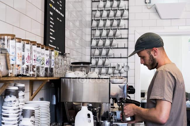 Молода чоловіча бариста, яка працює з кавовою машиною в кафе. — стокове фото