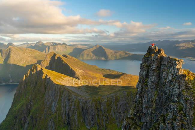 Man standing at top of pinnacle in landscape of Senja Island, Troms, Norway, Europe. — Stock Photo