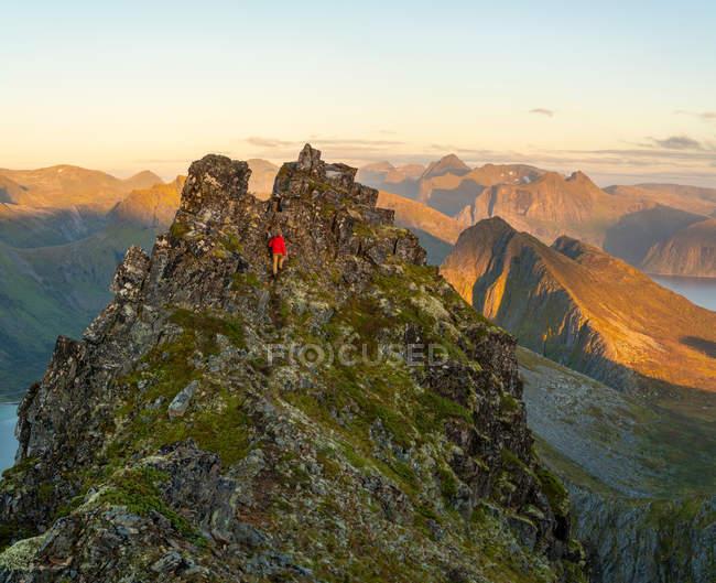 Uomo che sale a steep peak in un paesaggio frastagliato dell'isola di Senja, Troms, Norvegia, Europa. — Foto stock