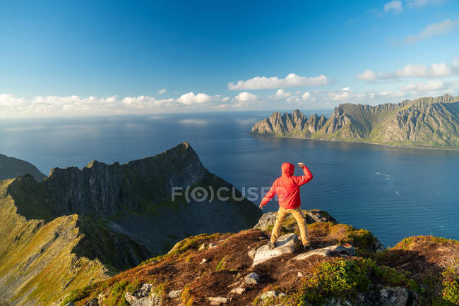 Man with arms outspread in celebration on top of mountains, Senja Island, Troms, Norway, Europe. — Stock Photo