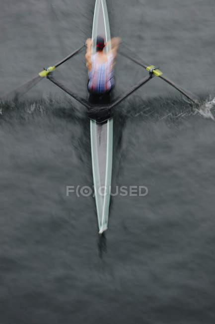 Vue de dessus de l'homme de barre dans un canot pneumatique en eau calme au milieu du parcours, flou de mouvement. — Photo de stock