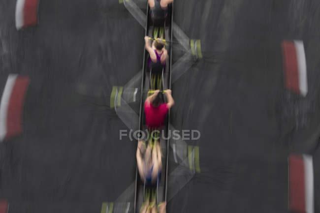 Vista aérea de movimiento borroso de la tripulación de remo en el barco de arrastre en el agua . - foto de stock