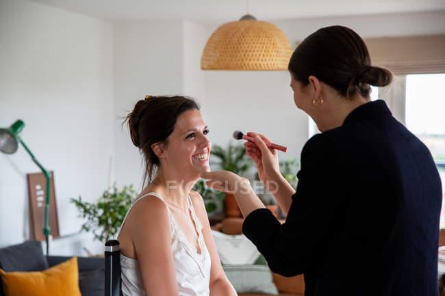 Truccatore professionista al lavoro, creando look con pennello per giovane donna . — Foto stock