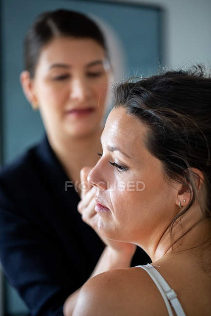 Truccatore professionista al lavoro, creando look per giovane donna . — Foto stock