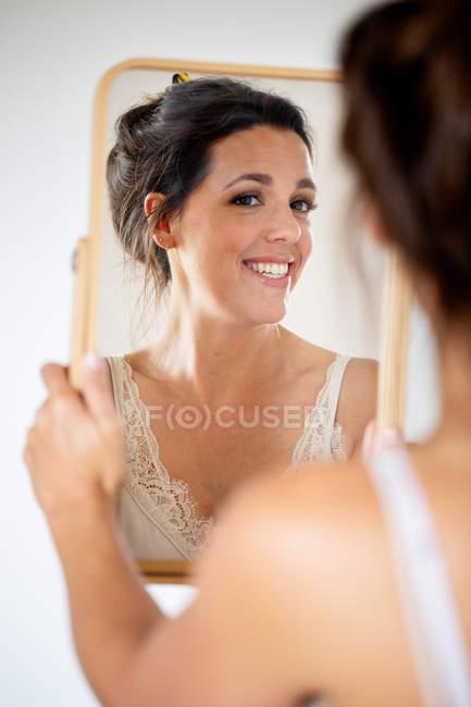 Portrait d'une femme souriante tenant et regardant dans le miroir. — Photo de stock