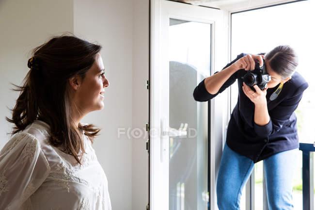 Artista de maquilhagem profissional no trabalho, tirando fotografia de mulher em estúdio . — Fotografia de Stock