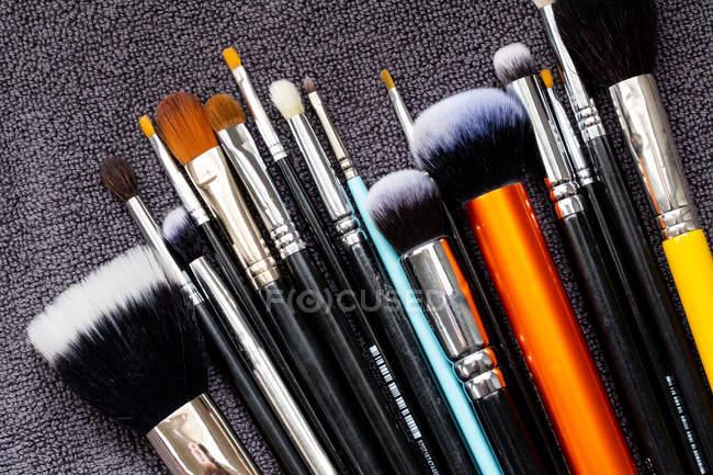 Alto ângulo close-up de seleção de pincéis de maquiagem em várias formas e tamanhos . — Fotografia de Stock