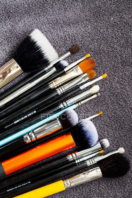 High angle close-up of selection of make-up brushes in various shapes and sizes. — Stock Photo