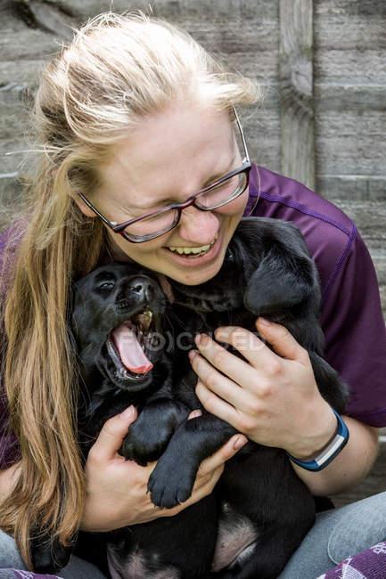 Blonde woman wearing glasses hugging two black labrador puppies. — Stock Photo