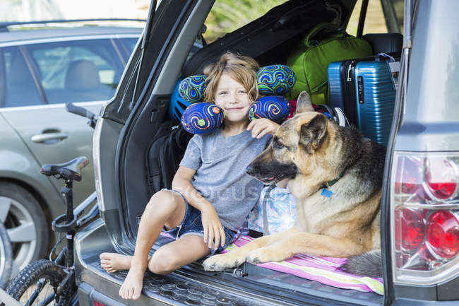 Elementary age boy with German Shepherd dog wearing travel pillows in back of  SUV. — стокове фото
