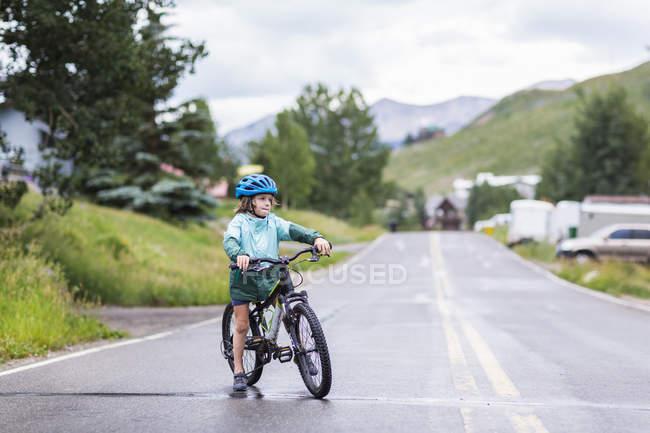 Мальчик младшего возраста катается на велосипеде по дождливой дороге . — стоковое фото