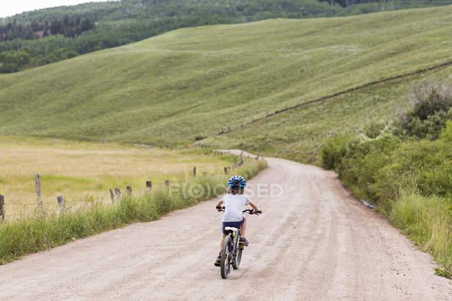 Погляд на хлопчика з початкового віку на велосипеді по сільській дорозі.. — стокове фото