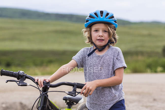 Menino de idade elementar segurando bicicleta no campo . — Fotografia de Stock