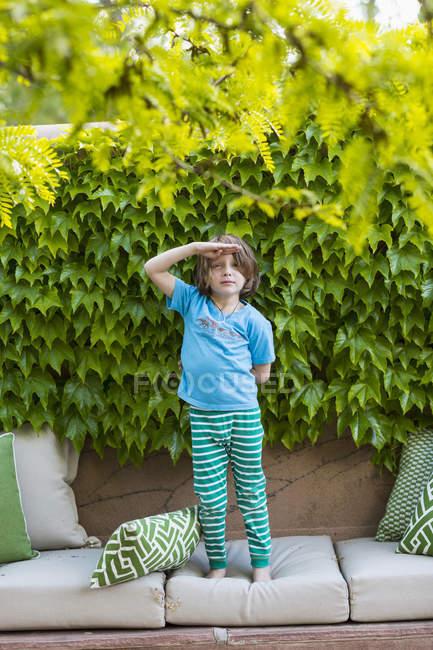 Edad elemental de pie en almohadas sofá delante de hojas verdes . - foto de stock