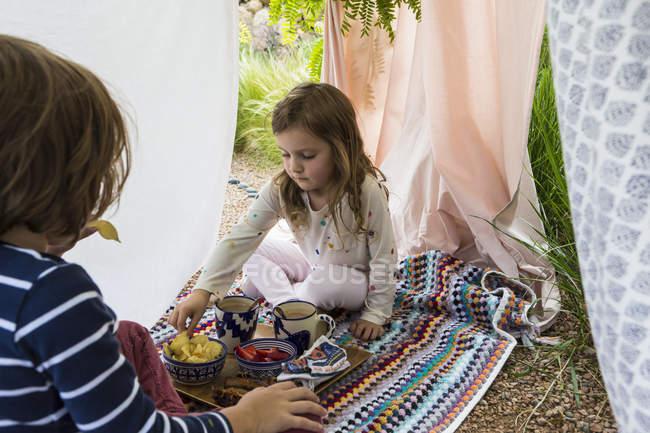 Мальчик и девочка играют в уличной импровизированной палатке — стоковое фото