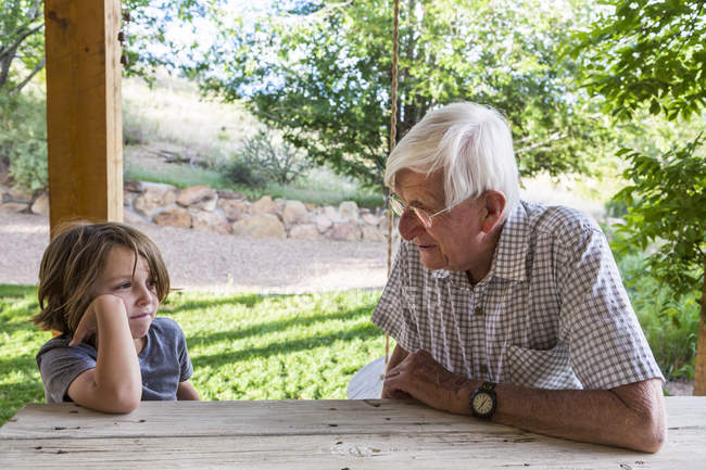 Grandfather and grandson sitting on wooden table and talking outdoors. — Stock Photo