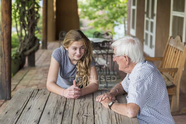 Blonde teenage girl having conversation with senior grandfather. — Stock Photo