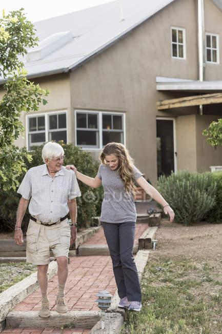Ragazza adolescente e nonno a piedi lungo il percorso per casa . — Foto stock