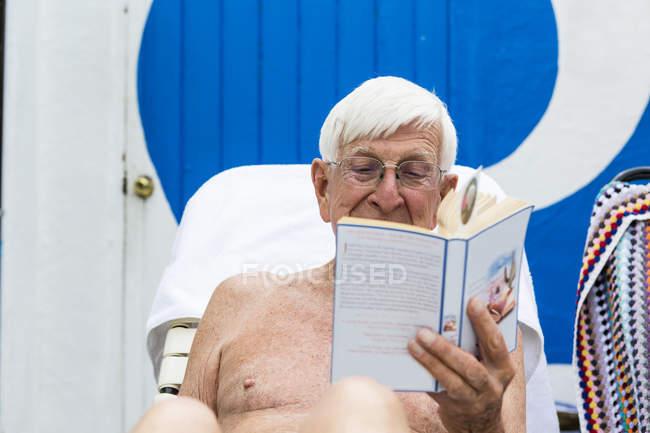 Senior man at poolside reading book — Stock Photo