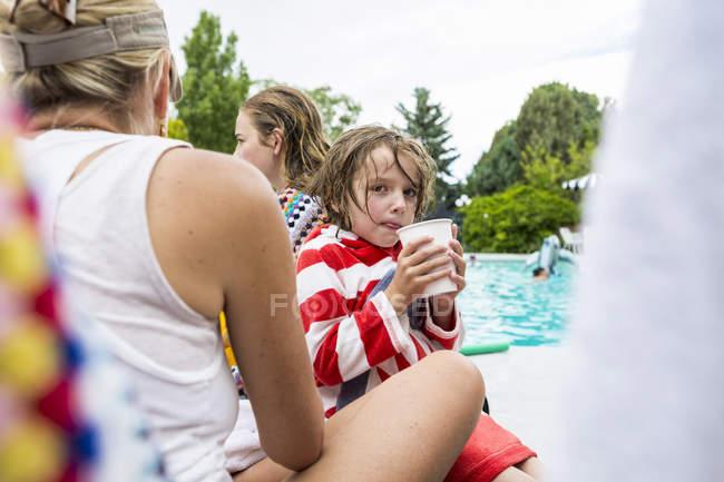 Petit garçon avec soeur adolescente et mère assise au bord de la piscine . — Photo de stock