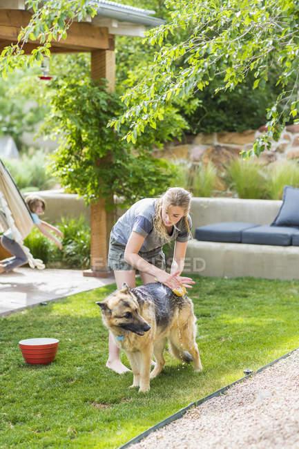 Blonde teenage girl washing dog on green lawn. — Stock Photo