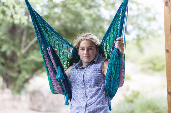Blonde teenage girl resting in hammock in country. — Stock Photo