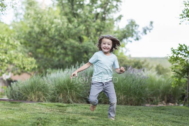 Glücklicher kleiner Junge läuft auf grünem Rasen. — Stockfoto