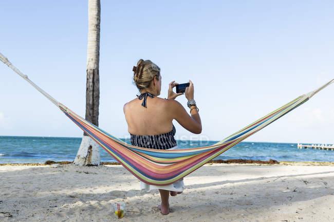 Женщина отдыхает в гамаке, фотографируясь со смартфоном на острове Гранд-Кейман — стоковое фото