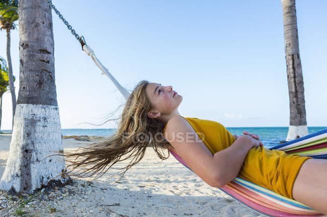 Blonde teenage girl resting in colorful hammock on beach. — Stock Photo