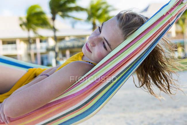 Bionda adolescente ragazza che riposa in amaca colorata sulla spiaggia. — Foto stock