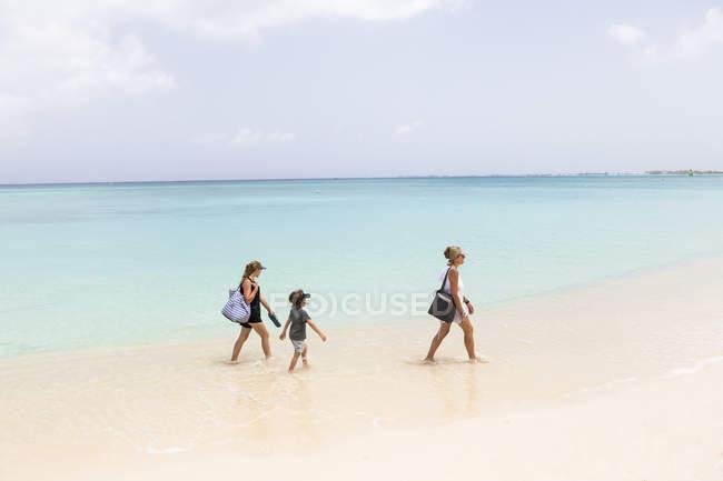 Мать с детьми, гуляющая по пляжу в воде, остров Гранд-Кейман — стоковое фото