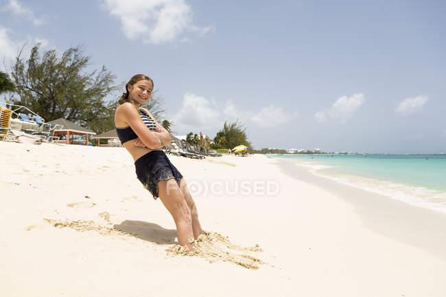 Smiling teen girl leaning in sand on resort. — Stock Photo