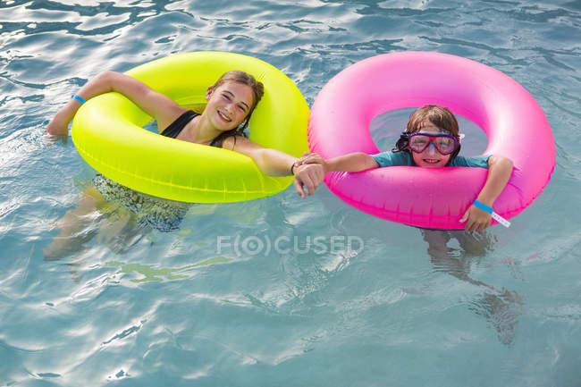 Geschwister spielen im Pool mit bunten Schwimmern. — Stockfoto