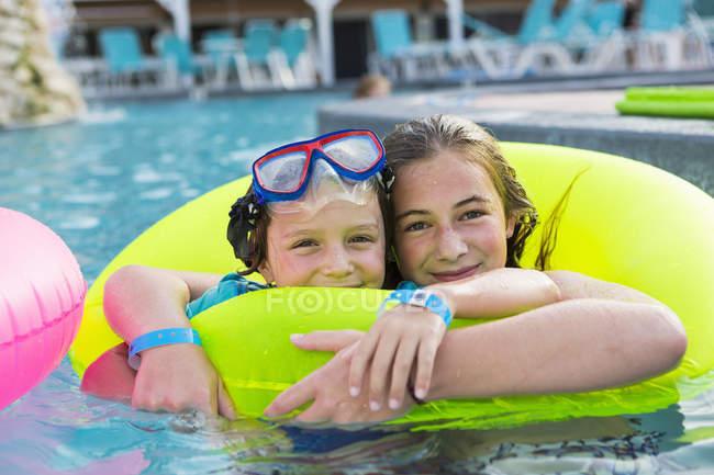 Брати і сестри грають у басейні на барвистій воді.. — стокове фото