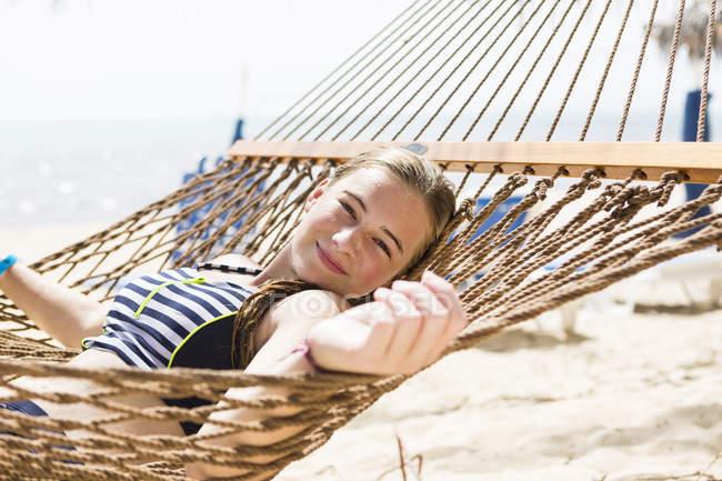 Blonde teenage girl relaxing in hammock on beach. — Stock Photo